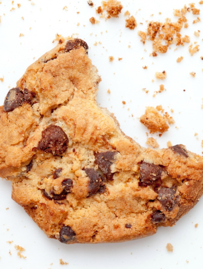 Close up of an half eaten cookie with crumb against a white background